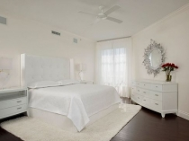 Спальня с белой отделкой стен и темным напольным покрытием