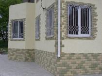 Штукатурка и камень в отделке дома с высоким цоколем