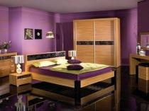 Эффектная спальня со светло-коричневой мебелью и сиреневыми стенами