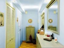 Узкий коридор с отделкой стен однотонными голубыми обоями