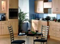 Голубые обои и мебель теплых тонов в кухне