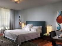 Простой и лаконичный интерьер спальни с серой отделкой стен и потолка