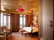 Марокканский интерьер спальни с художественной росписью потолка