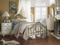 Интерьер спальни с белой мебелью и кованой кроватью