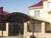 Арочная конструкция пристроенного к дому металлического навеса