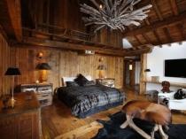 Красивая спальня с обшивкой потолка и стен деревом