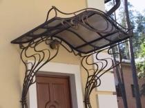 Навес с красивым кованым оформлением для крыльца дома