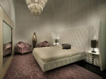 Кровать с длинным кожаным изголовьем в спальне