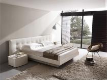 Белая кровать с длинным мягким изголовьем в спальне