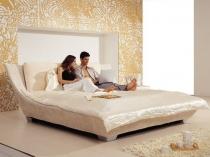 Большая двухспальная кровать с изогнутой спинкой в спальне
