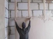 Нанесение штукатурки на стену по установленным маякам