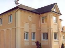 Бежевые оттенки мозаичной штукатурки в отделке фасада дома