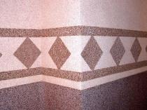 Отделка стены мозаичной штукатуркой с аккуратным геометрическим рисунком