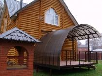 Полукруглый поликарбонатный навес для крыльца дома из бревен