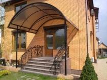 Поликарбонатный навес полукруглой формы над входной дверью дома