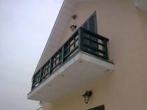Балкон частного дома с деревянным парапетом