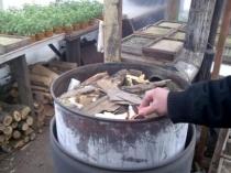 Топка на дровах печи в дачной теплице