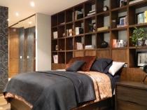 Оборудование стены у изголовья кровати в спальне системой вместительных полок