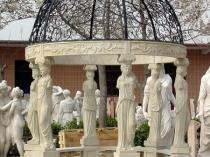 Круглая беседка с кованой крышей и скульптурами