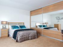 Большой встроенный шкаф с зеркальной вставкой в спальне
