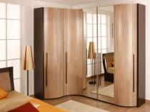 Угловой шкаф с фасадом обтекаемой формы в спальне