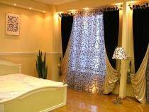 Контрастные двухсторонние шторы в спальне с однотонной отделкой стен
