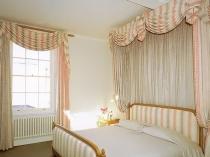 Полоска в дизайне штор и драпировке мебели в спальне