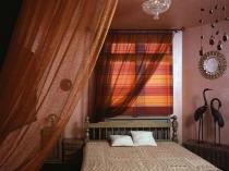 Комбинация римских штор с легкими занавесками в спальне