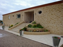 Облицовка фасада загородного дома рельефной штукатуркой под камень
