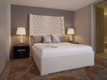 Двуспальная кровать с высоким мягким изголовьем в спальне