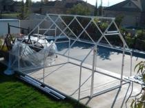 Установка на участке каркаса для строительства двускатной теплицы
