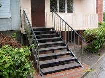 Крыльцо дома с металлическими ступенями и перилами
