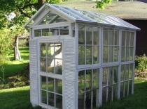 Маленькая теплица с крышей и стенами из оконных рам