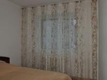 Бежевая с рисунком тюлевая занавеска в спальне с белой отделкой стен
