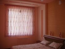 Короткая полупрозрачная тюлевая занавеска в спальне