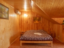 Спальня на мансарде с деревянной вагонкой на стенах и потолке