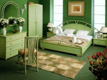 Светло-зеленая мебель и стены более темного оттенка в спальне