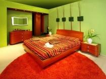 Смелое сочетание зеленого и красного цвета в дизайне спальни