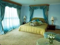 Большая спальня с пышными классическими шторами бирюзового цвета