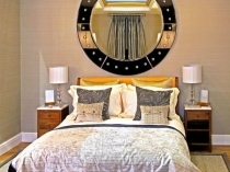 Круглое зеркало с подсветкой на стене спальни