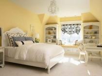 Нежная спальня с белой мебелью и отделкой стен желтым цветом