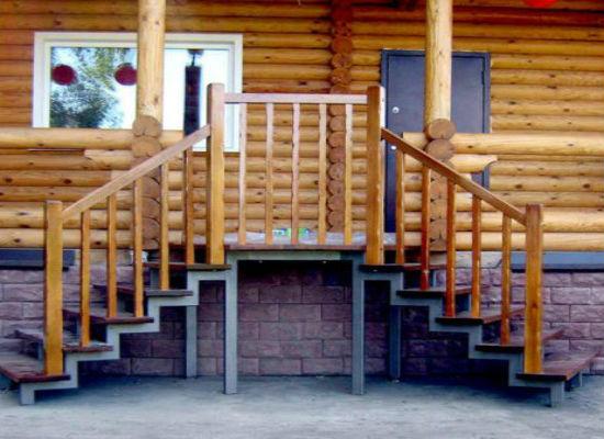 Металлическая лестница крыльца с деревянными перилами