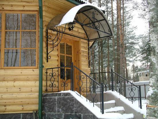 Деревянный дом с каменным крыльцом и элементами ковки
