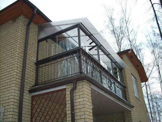 Балкон с кованым парапетом и остеклением