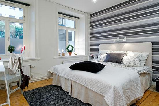 Декорирование стены спальни серыми в полоску обоями