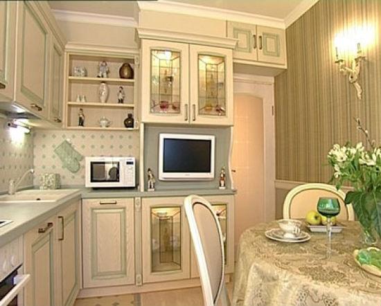Светлая мебель и золотистые обои в кухне