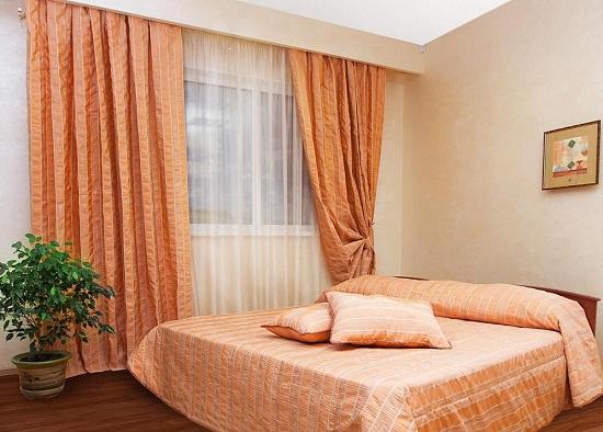 Шторы оранжевого цвета для создания позитивной атмосферы в спальне