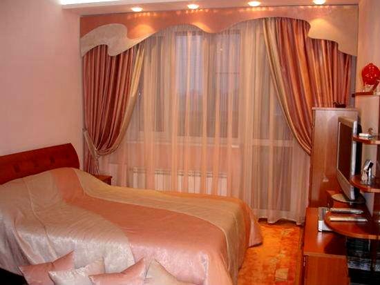 Простая тюль с декоративным ламбрекеном в оформлении окна спальни