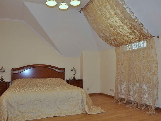 Ажурные полупрозрачные шторы в спальне на мансарде