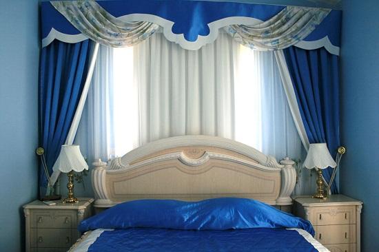 Ярко-синие шторы в спальне с голубой отделкой стен